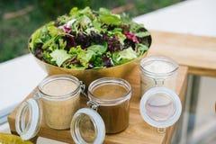 Зеленый салат служил в шаре на деревянном столе с 3 различными шлихтами стоковая фотография