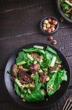 Зеленый салат с печенью и шпинатом на темной деревенской предпосылке Стоковая Фотография