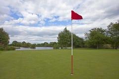 Зеленый цвет гольфа с красным флагом гольфа стоковые изображения