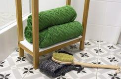 Зеленый цвет красиво сложил полотенца на белой полке с щеткой и washcloth массажа стоковые фотографии rf