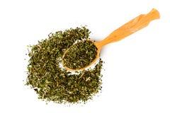 Зеленый чай в деревянной ложке и разбросанный на белую изолированную предпосылку, Стоковые Изображения RF