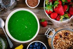 Зеленый шар smoothies шпинат, бананы, клубники, голубики, granola и семена Стоковые Изображения RF