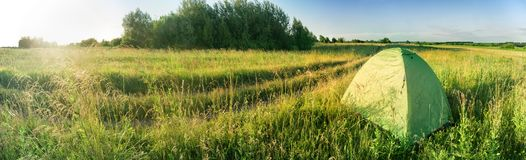 Зеленый шатер в зеленом поле около дороги на заходе солнца Стоковое Изображение RF