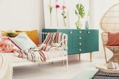 Зеленый шкаф с ручкой формы кроны в середине яркой спальни с красочными постельными принадлежностями на стуле павлина кровати и р стоковые фотографии rf