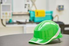 Зеленый шлем безопасности на промышленной предпосылке Стоковая Фотография RF