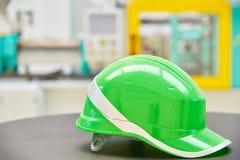 Зеленый шлем безопасности на промышленной предпосылке Стоковое Изображение