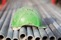 Зеленый шлем безопасности на трубках металла Стоковое Изображение
