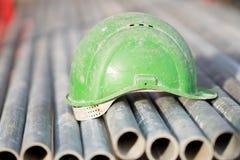 Зеленый шлем безопасности на трубках металла Стоковые Фотографии RF