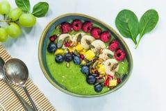 Зеленый smoothie авокадоа, шпината и виноградины гарнированный с свежими фруктами стоковые изображения