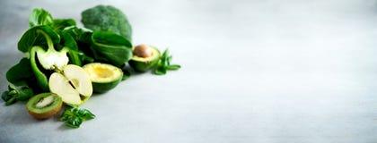 Зеленый smoothie в стеклянном опарнике с свежими органическими зелеными овощами и плодоовощами на серой предпосылке Диета весны,  Стоковые Фотографии RF