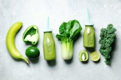 Зеленый smoothie в стеклянном опарнике с свежими органическими зелеными овощами и плодоовощами на серой предпосылке Диета весны,  Стоковые Фото