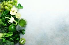 Зеленый smoothie в стеклянном опарнике с свежими органическими зелеными овощами и плодоовощами на серой предпосылке Диета весны,  Стоковое Изображение