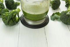 Зеленый smoothie в blender и сырцовом брокколи на деревянной предпосылке Космос для текста стоковое изображение