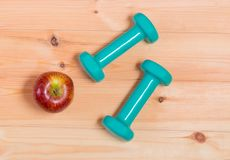 2 зеленых гантели и яблока на деревянной предпосылке Стоковое Изображение RF