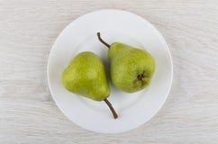 2 зеленых груши в белой стеклянной пластинке на деревянном столе Стоковое Изображение
