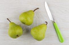 3 зеленых груши и ножа таблицы на деревянном столе Стоковые Фотографии RF