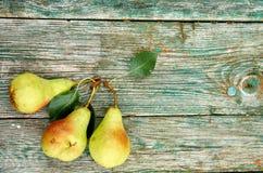 3 зеленых груши с листьями на деревянном зеленом коричневом цвете постарели конец предпосылки текстуры вверх Стоковые Изображения RF