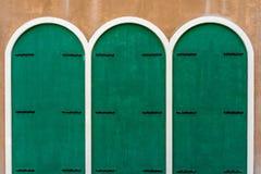 3 зеленых деревянных двери на коричневой бетонной стене Стоковые Изображения