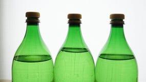 3 зеленых пластичных бутылки заполнили с водой к верхней части Стоковое фото RF