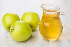 3 зеленых яблоки и яблочного сока в кувшине на таблице Стоковые Фотографии RF