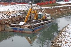 Землекоп бульдозера в барже в ходе работы реки Стоковая Фотография