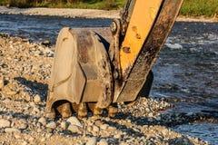 Земля камней ведра машины экскаватора землекопа выкапывая рекой стоковое фото rf