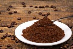 Земной кофе на белой плите с sorrounding кофейными зернами Стоковая Фотография RF