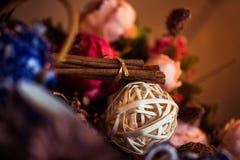 Земной циннамон, ручки циннамона, соединился с подносом с смычком на флористической предпосылке в деревенском стиле селективно Стоковое фото RF