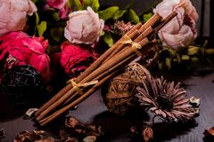 Земной циннамон, ручки циннамона, соединился с подносом с смычком на флористической предпосылке в деревенском стиле селективно Стоковые Фотографии RF