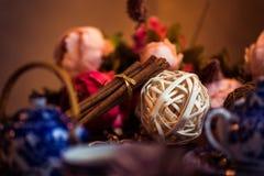 Земной циннамон, ручки циннамона, соединился с подносом с смычком на флористической предпосылке в деревенском стиле селективно Стоковая Фотография