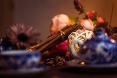 Земной циннамон, ручки циннамона, соединился с подносом с смычком на флористической предпосылке в деревенском стиле селективно Стоковое Фото