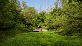 Землянка Derevyannaya, на зеленых холмах Стоковая Фотография