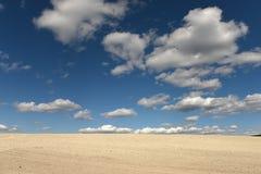 Земля глины и белые облака на голубом небе Стоковые Изображения