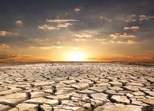 Земля засухи против захода солнца Стоковая Фотография