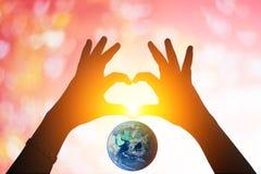 Земля и руки под в форме сердц силуэтом Стоковое Изображение RF