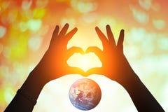 Земля и руки под в форме сердц силуэтом Стоковые Фотографии RF