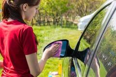 Зеркало взгляда со стороны автомобиля чистки женщины стоковые фото