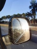 Зеркало заднего вида автомобиля с отражать солнца и захода солнца лет стоковое изображение rf