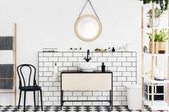 Зеркало над washbasin в белом интерьере ванной комнаты с заводами и черный стул рядом с лестницей Реальное фото стоковые изображения rf