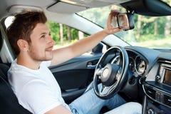 Зеркало отладки молодого человека в автомобиле Стоковое Изображение