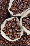 Зерна кофе в сумках Зерна предпосылки кофе Стоковые Изображения RF