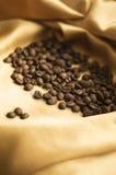 Зерна кофе лежа на золотой ткани Стоковое фото RF