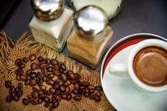 Зерна кофе на дерюге около чашки кофе Стоковое фото RF