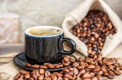 Зерна кофе на деревянной доске и чашке кофе Стоковое Изображение RF