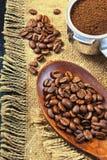 Зерна кофе на предпосылке джута grinded кофе Стоковое Изображение