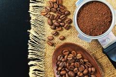Зерна кофе на предпосылке джута grinded кофе Стоковые Фотографии RF