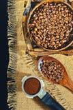 Зерна кофе на предпосылке джута grinded кофе Стоковая Фотография