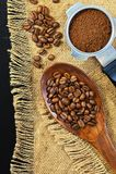Зерна кофе на предпосылке джута grinded кофе Стоковая Фотография RF