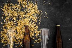 Зерна пивоваренного ячменя около пивной бутылки и стекла на черном взгляд сверху предпосылки Стоковое фото RF