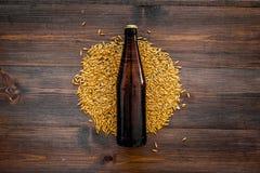 Зерна пивоваренного ячменя около пивной бутылки на деревянном copyspace взгляд сверху предпосылки Стоковое фото RF